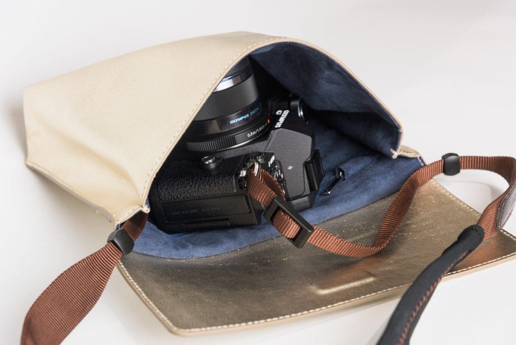 Kultainen kameralaukku jonka sisällä Olympus OM-D