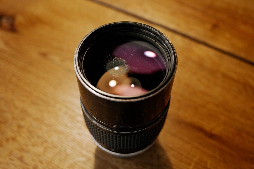 Nikonin objektiivi, naarmuja linssissä. Nikkor 180mm f/2.8. Kuva: Anssi Lepikko.