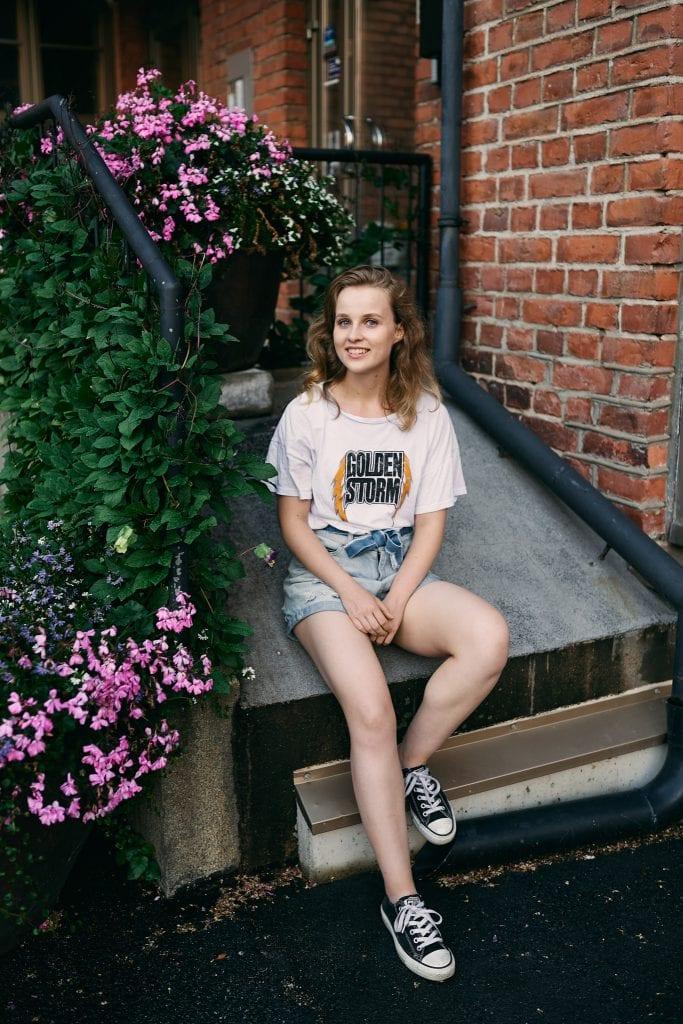 Kuva kukkien luona istuvasta hymyilevästä tytöstä.