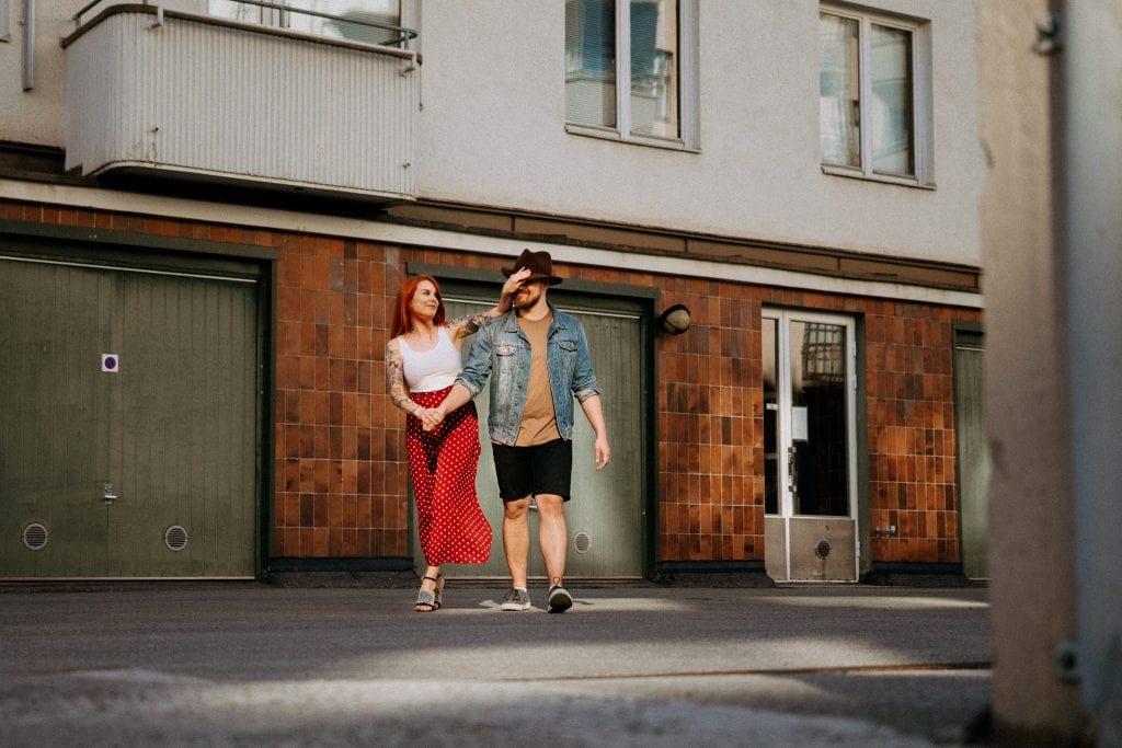 Pariskunta kävelee kohti kameraa ja nainen vetää stetsonin miehen silmille.