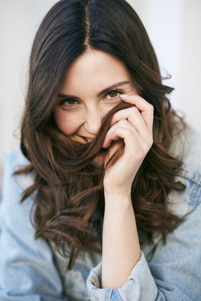 Nainen nauraa ja leikkii hiuksillaan.