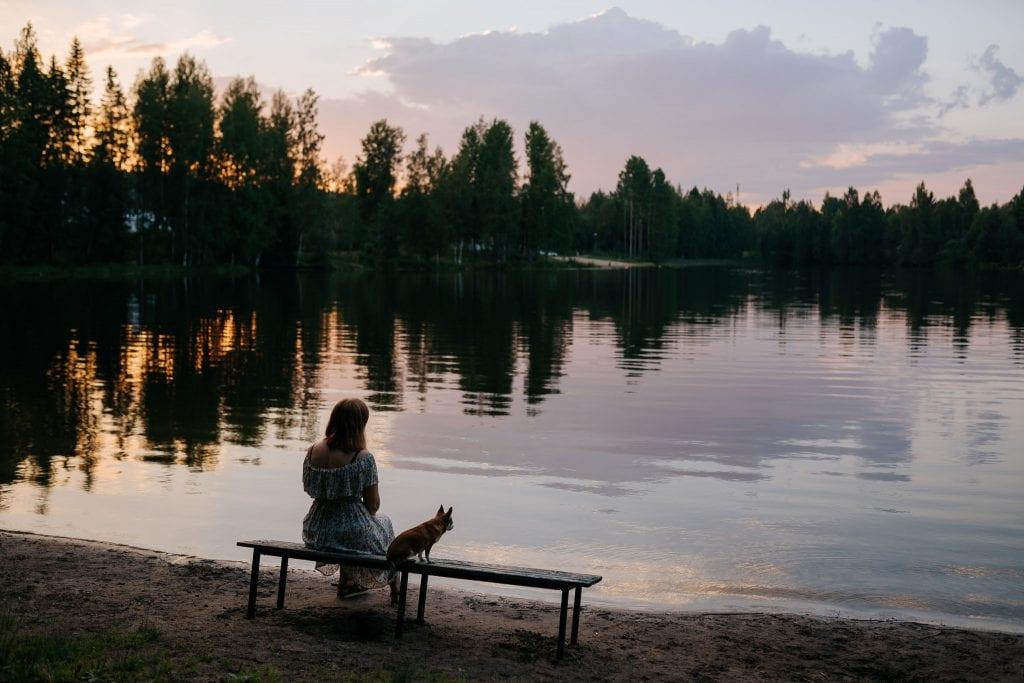 Nainen katselee koiransa kanssa järvelle auringonlaskun aikaan.