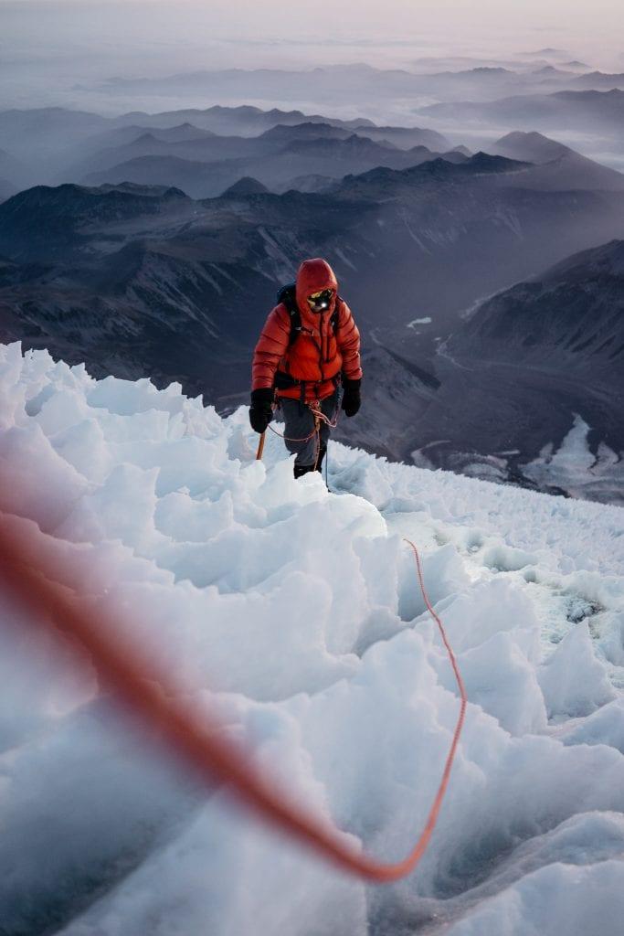 Jäinen vuoristomaisema ja kiipeilijä
