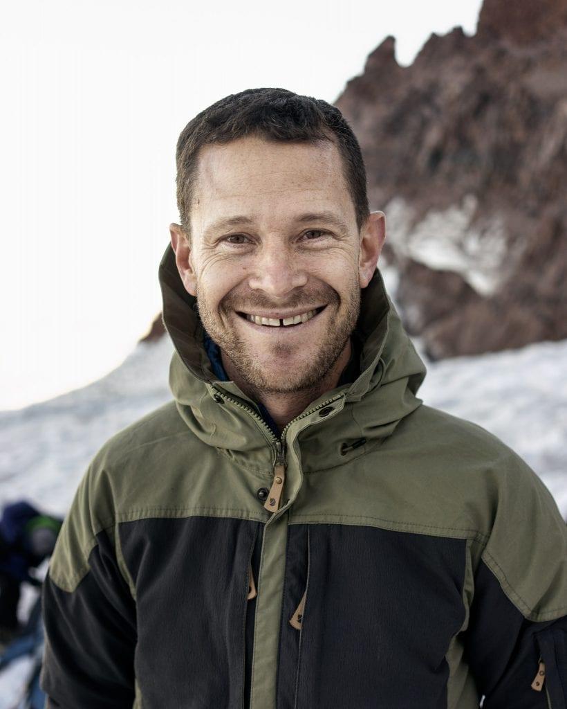 Hymyilevä Larry lumisessa vuoristomaisemassa.