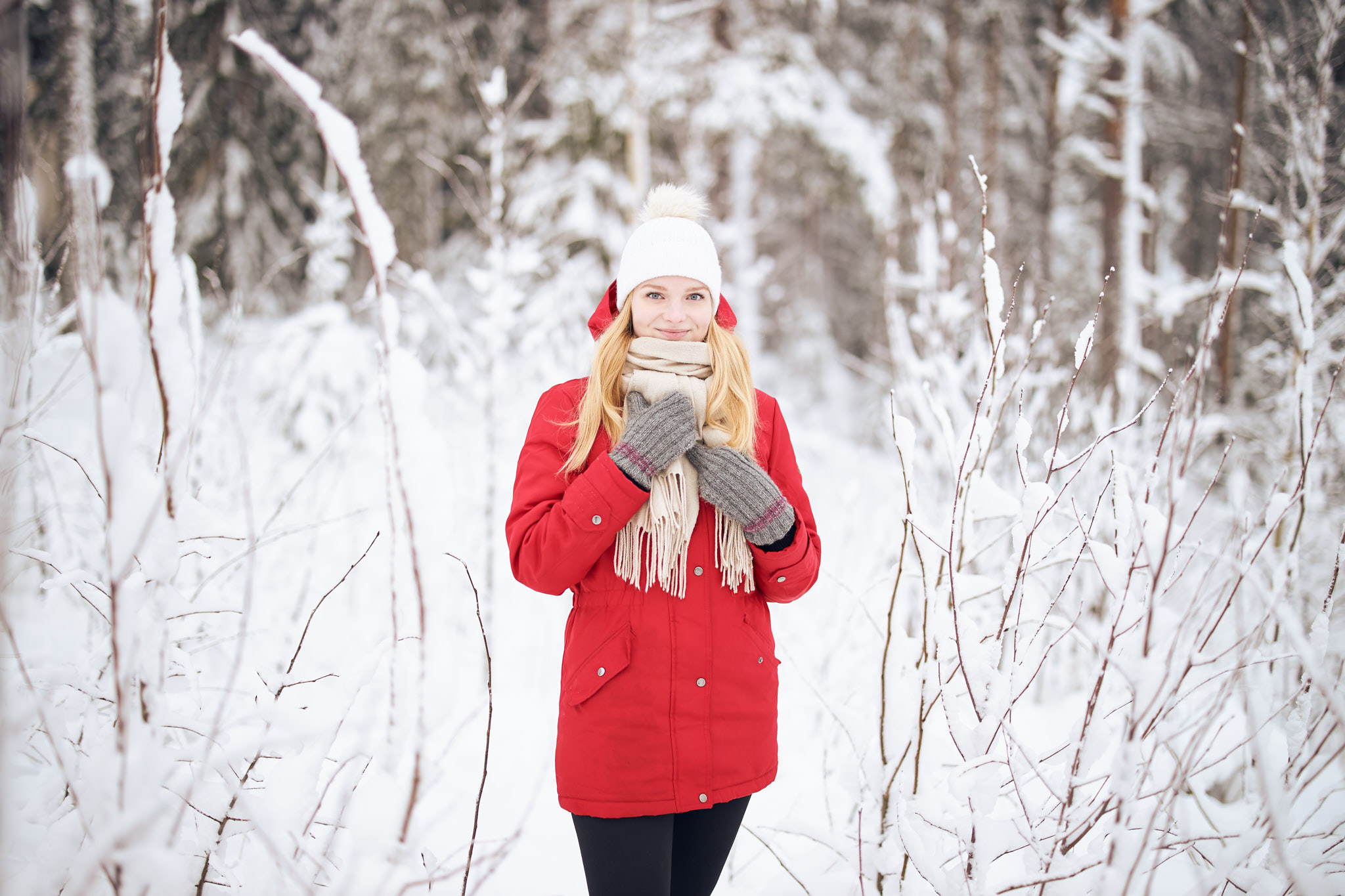 Punatakkinen nainen lumen keskellä.