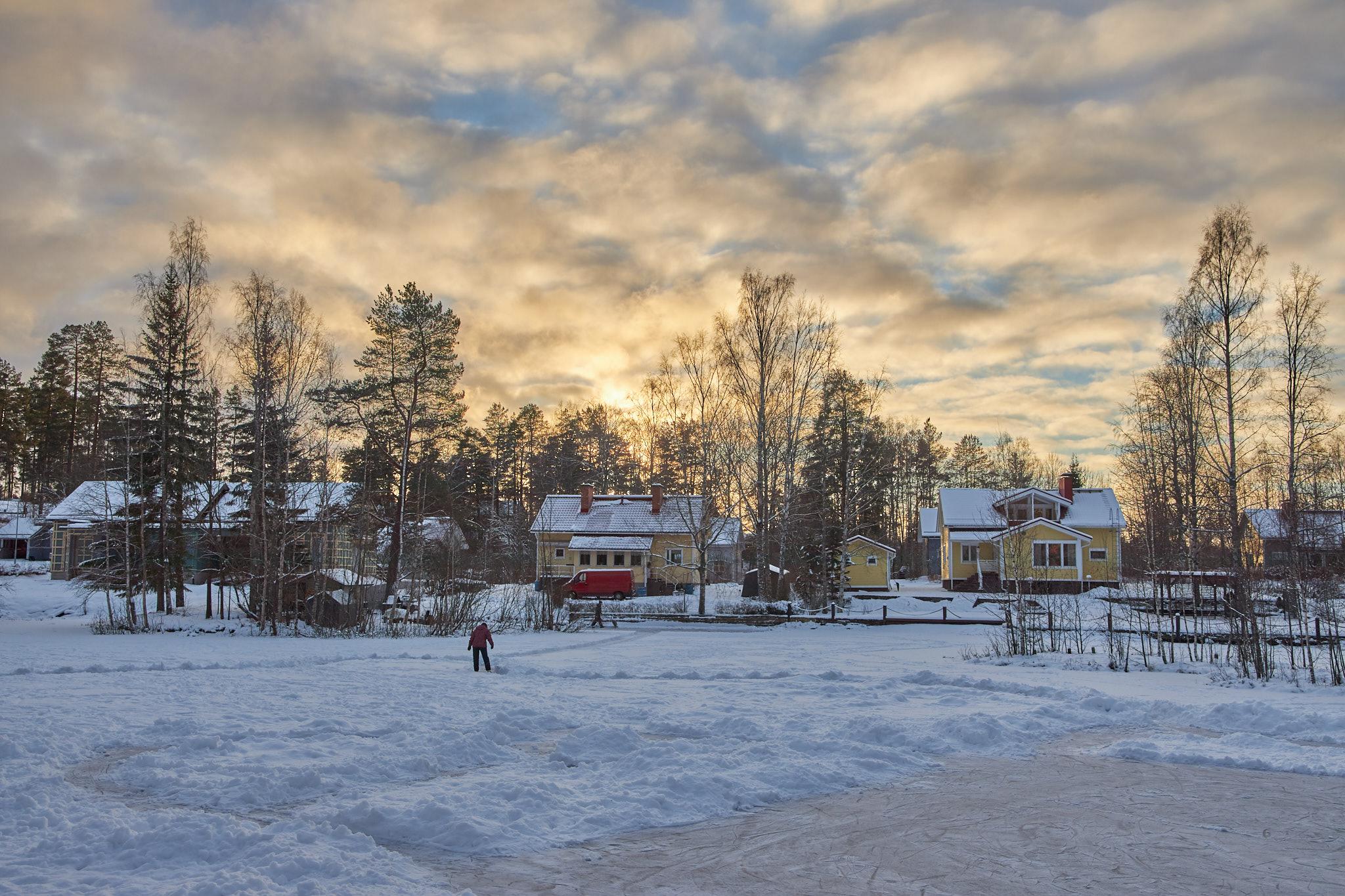 Talvinen alivalotettu maisema iltapäivän auringossa.