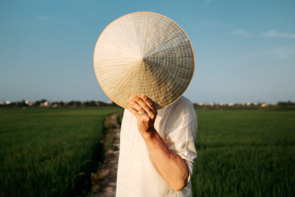 Anssi Lepikko pitää riisihattua kasvojensa päällä taustalla Hoi Anin riisipellot Vietnamissa.