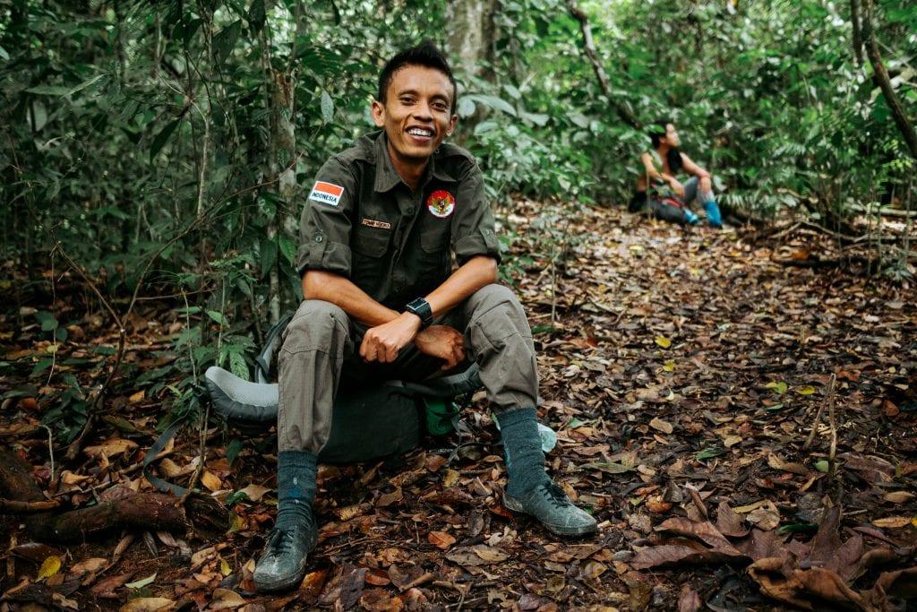 Indonesialainen viidakkoretkiopas istuu reppunsa päällä Bukit Lawangin viidakossa