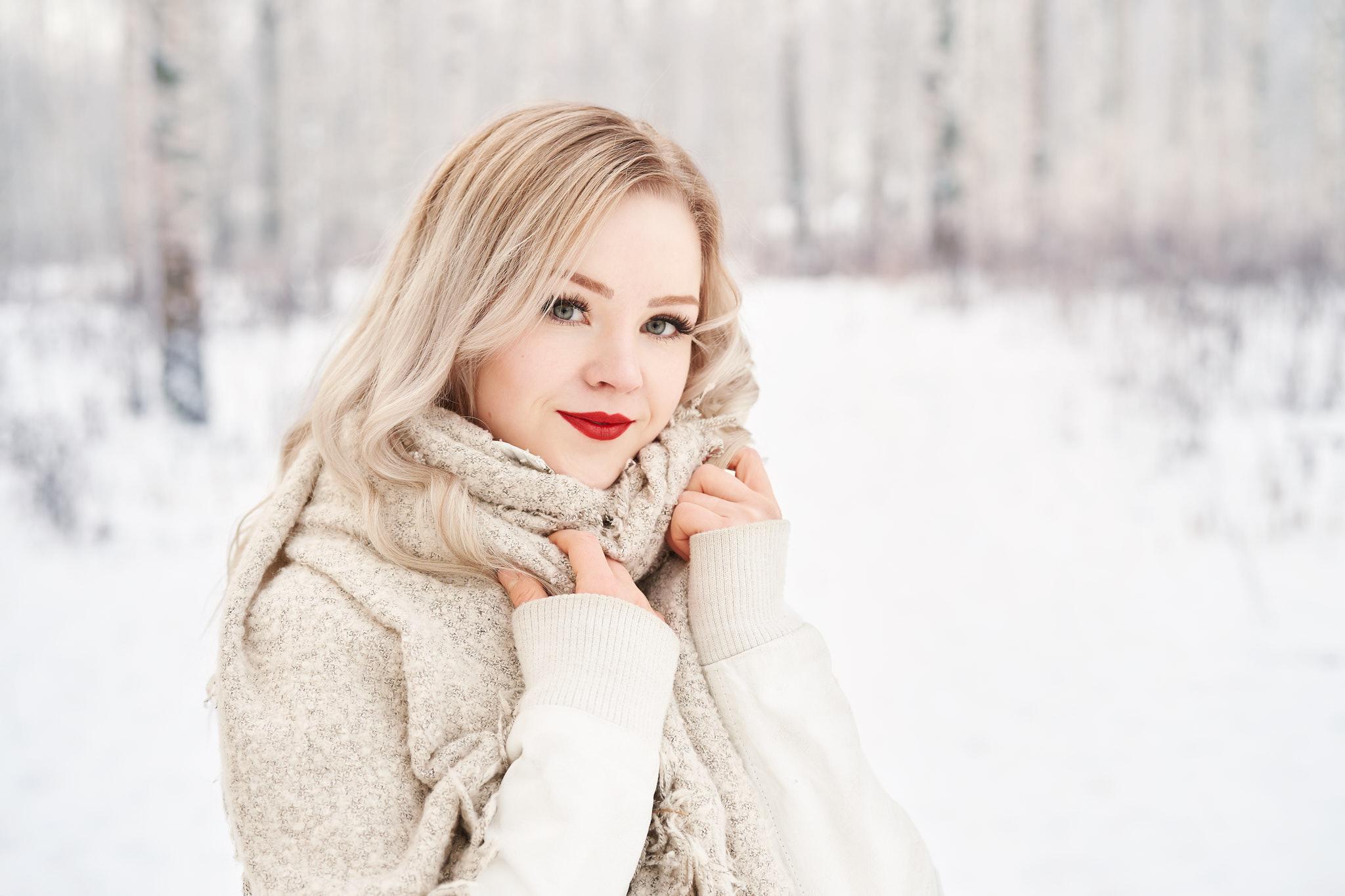 Nainen poseeraa talvisessa metsämaisemassa.