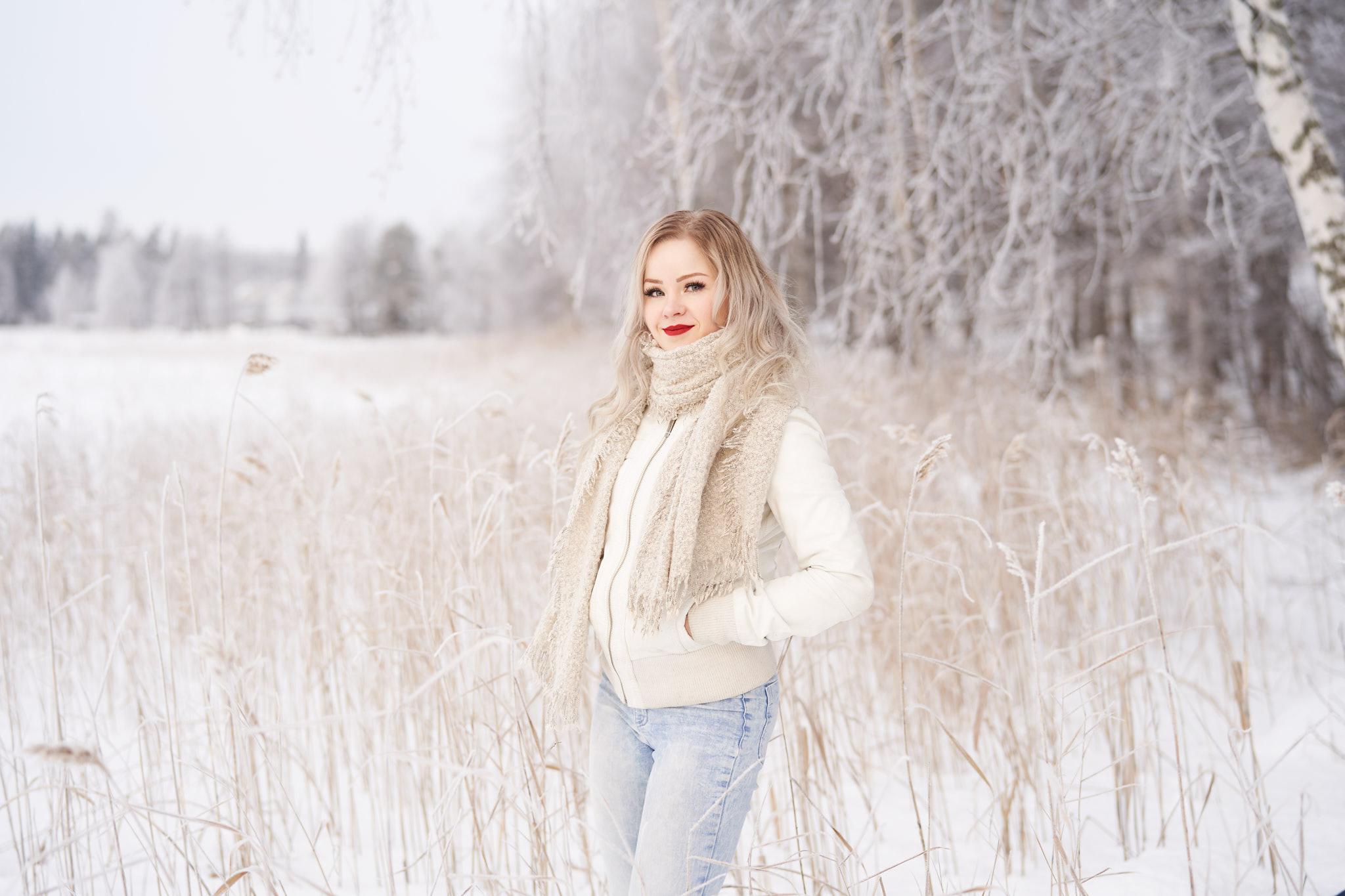 Nainen poseeraa talvisessa rantakaislikossa.