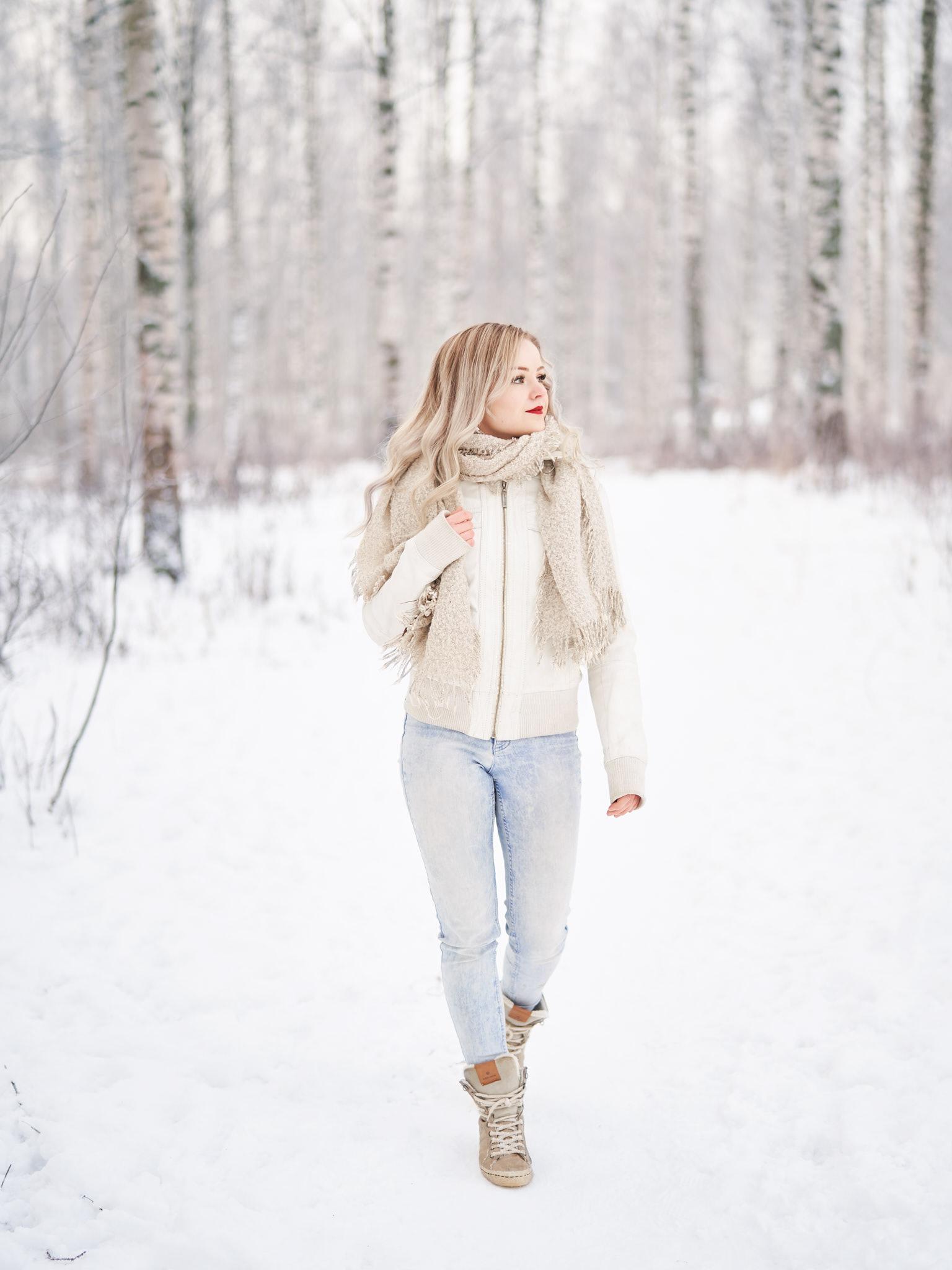 Nainen kävelee talvisessa metsässä ja katselee ympärilleen.