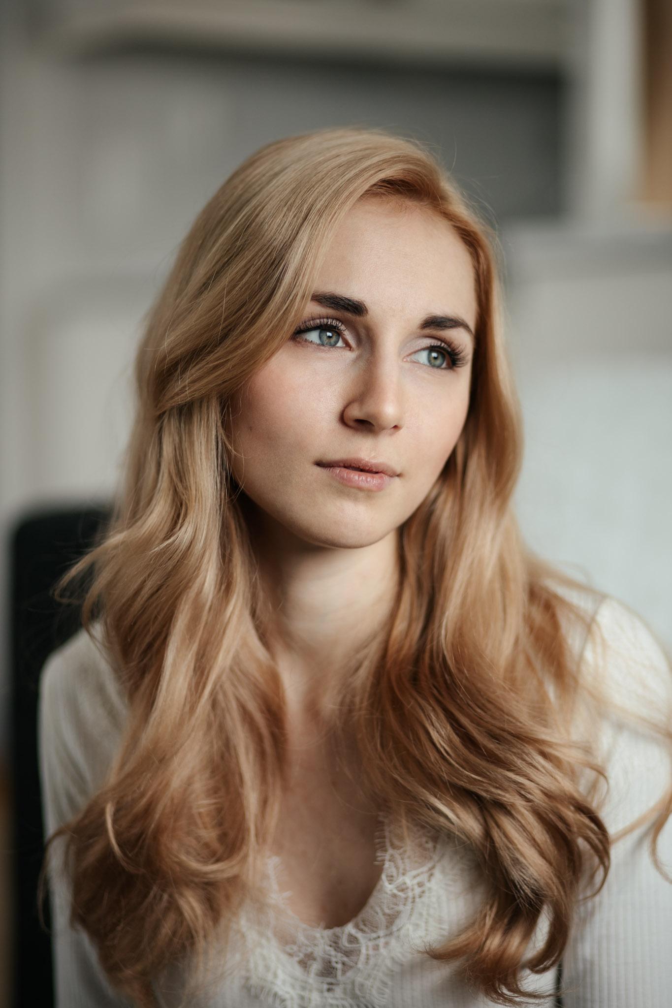 Vaaleahiuksinen nainen katsoo kaukaisuuteen.
