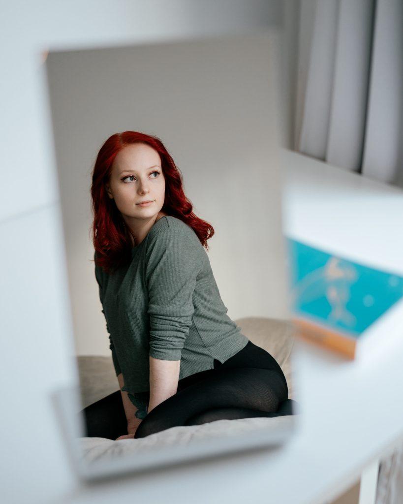 Punatukkainen tyttö istuu sängyllä kuvattuna pienen pöytäpeilin kautta.