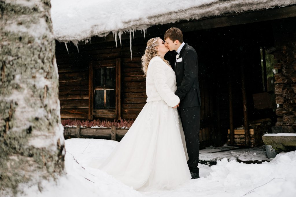 Valokuvaaja Anssi Lepikon tekemä hääkuva Majakoskella. Hääpari suutelee savusaunan edessä talvikelissä.