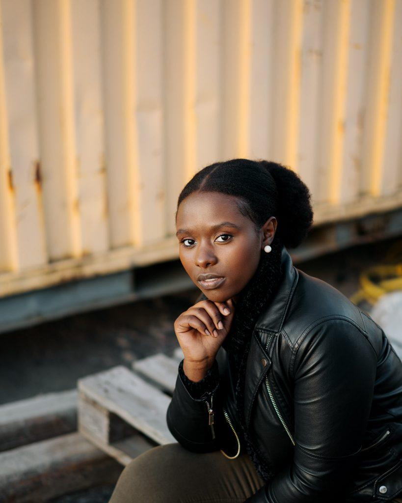 Kaunis tummaihoinen tyttö istuu rakennustyömaalla ja katsoo kameraan.